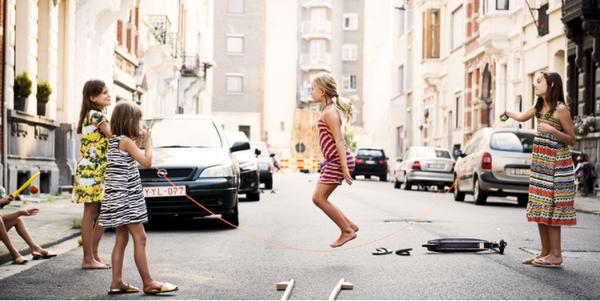 Vier kinderen spelen samen met een springtouw in een afgesloten speelstraat