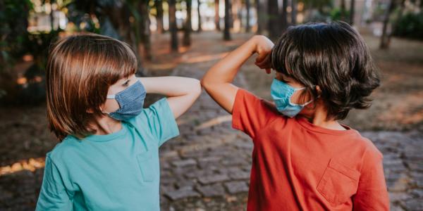 Twee kinderen met mondmasker groeten elkaar met elleboog