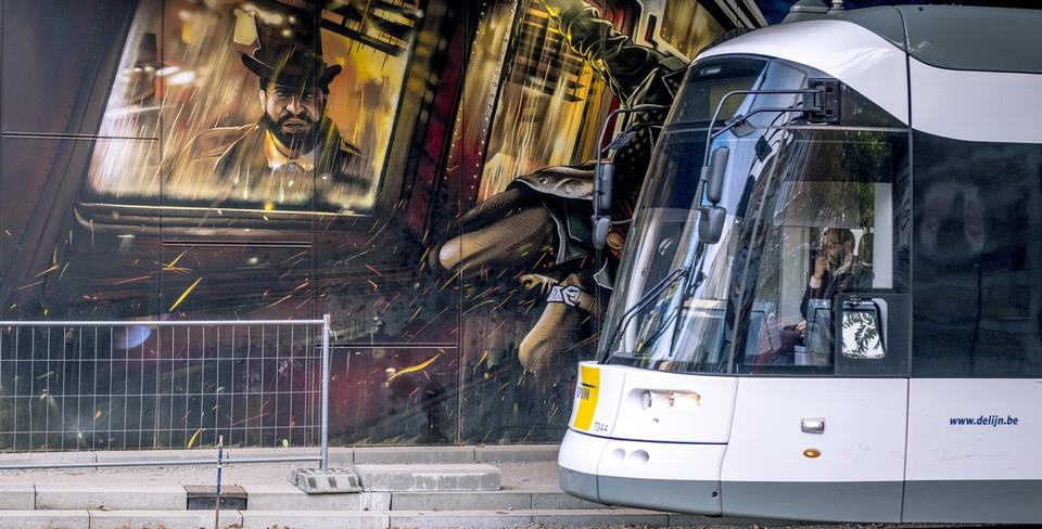 Tram rijdt voorbij een graffiti van Assassin's Creed