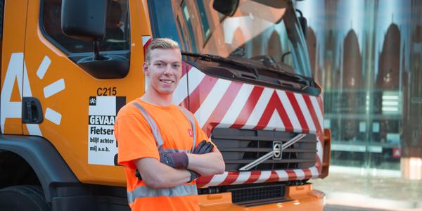 Jobstudent stad Antwerpen staat bij een huisvuilwagen