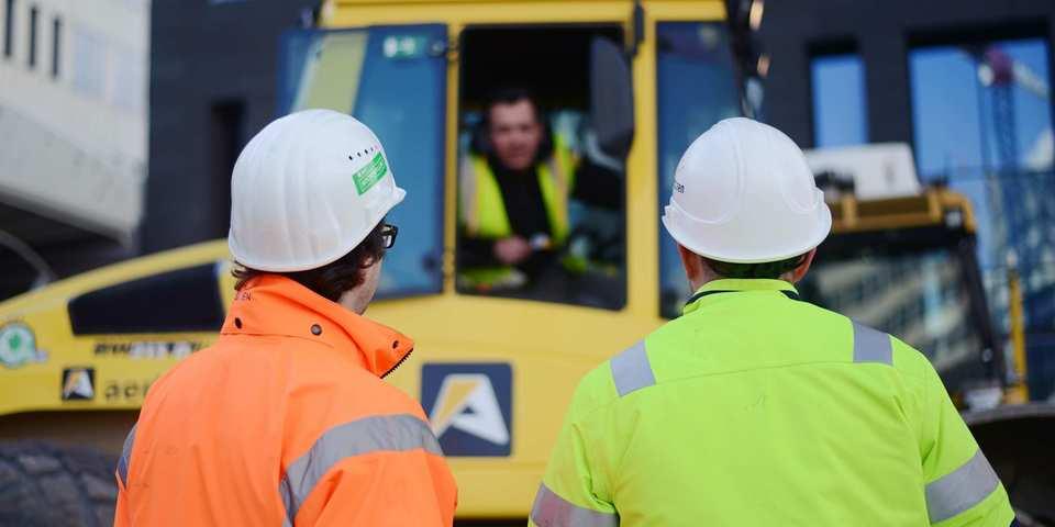 werftoezichter praat met werkers op de werf