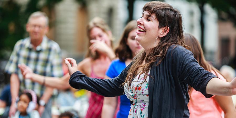 Een vrouw geniet zichtbaar terwijl ze aan het dansen is.