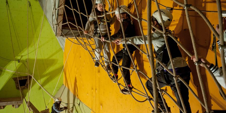 Drie kinderen klimmen in een touwparcours. Ze dragen helmen.