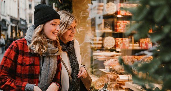 Twee vrouwen kijken naar winterse etalage