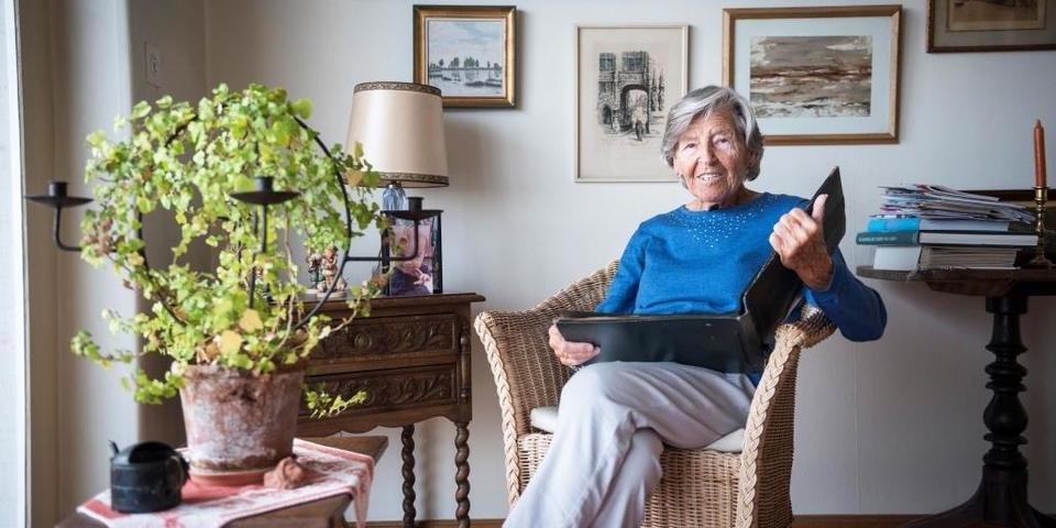 Mevrouw Leonie Vlijminckx bladert door fotoalbum
