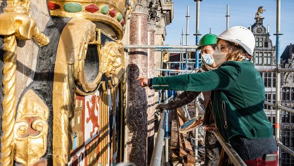 2 restaurateurs bekijken een wapenschild aan de gevel van het stadhuis van Antwerpen