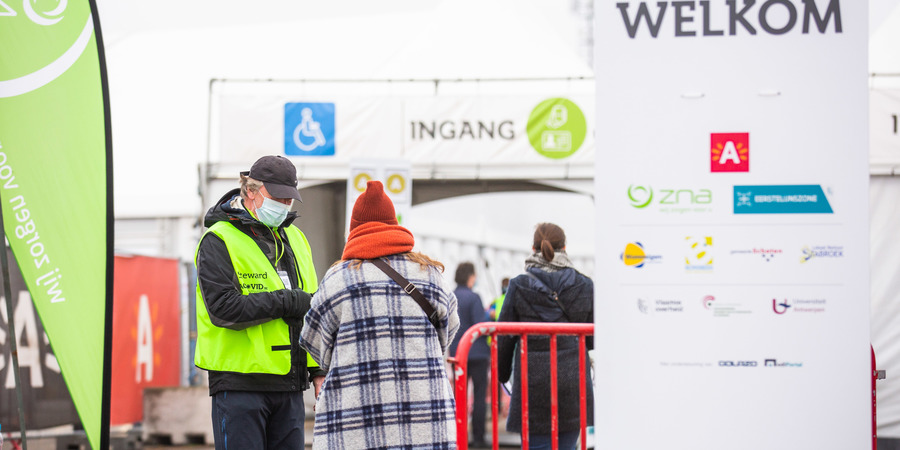 Een vrouw en een medewerker van het vaccinatiedorp VacCovid staan aan de ingang.