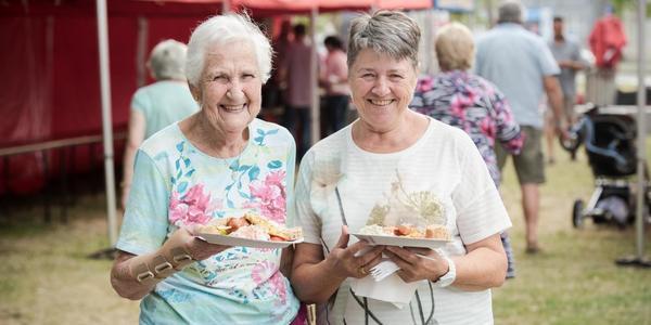 twee dames genieten van de barbecue op Feest in de Tent