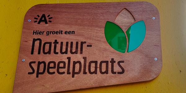 houtenbord met de tekst: hier groeit een natuurspeelplaats