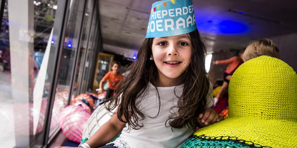 Een meisje met een papieren verjaardagskroon op haar hoofd.