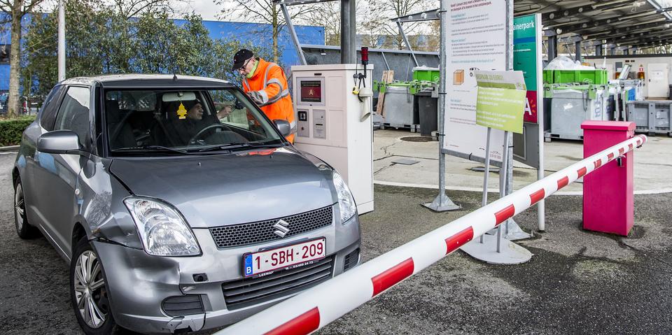wagen aan slagboon recyclagepark, medewerker helpt verder