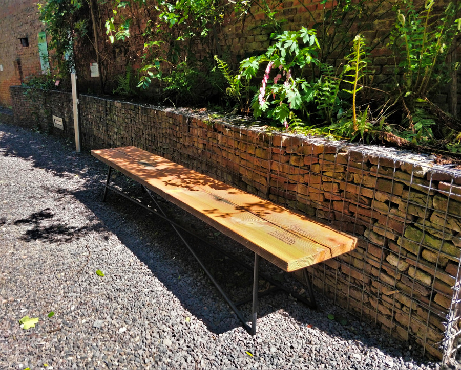 We zien een houten bank voor schanskorven gevuld met recuperatie baksteen.