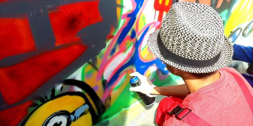Een jongere aan de slag met graffiti-spuitbussen.