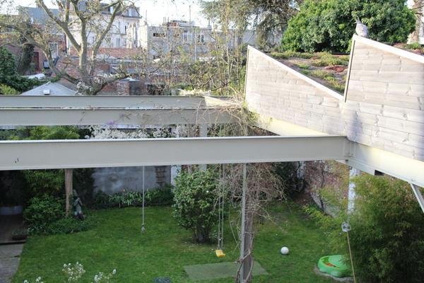 Klimplant slingert langs stalen balken boven een stadstuin