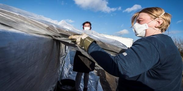 twee mensen verwijderen op een veilige manier asbesthoudende platen van een dak