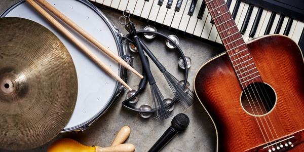 Een verzameling muziekinstrumenten waaronder gitaar, drums, een piano en een microfoon.