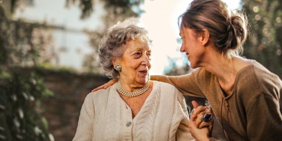 Een vrouwelijke mantelzorger legt haar arm om een bejaarde vrouw terwijl ze beiden glimlachen.