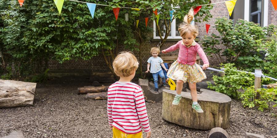 Een meisje springt van een boomstam