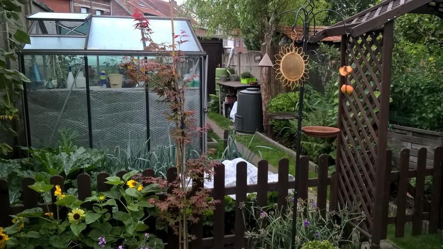 planten, een serre en bakken om te composteren in een kringlooptuin