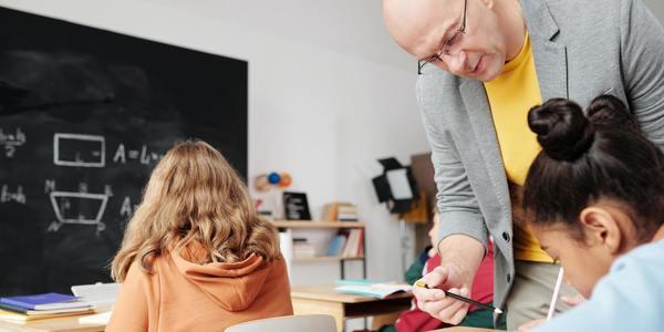leraar in de klas geeft instructies aan leerling