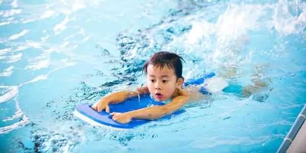 Klein jongetje leert zwemmen in zwembad met plankje