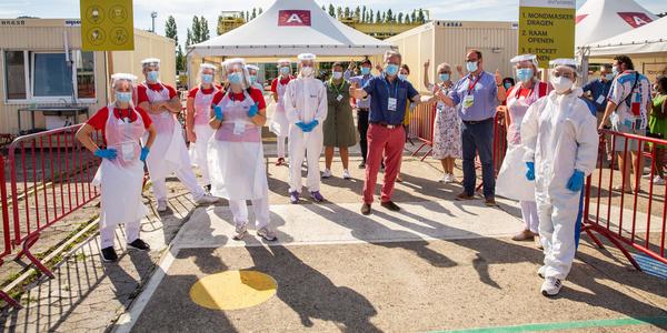 Tientallen vrijwilligers staan aan de ingang van het testdorp TestCovid.