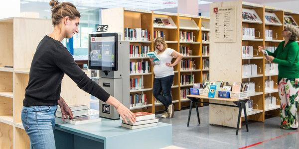 Bezoeker scant materialen in bibliotheek Vrede