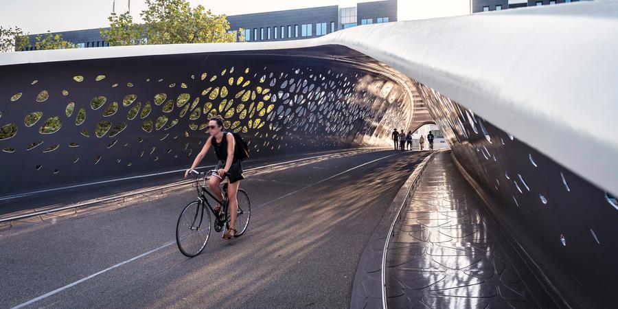 Een vrouw fietst over de Parkbrug in Antwerpen. Op de achtergrond wandelen enkele voetgangers.