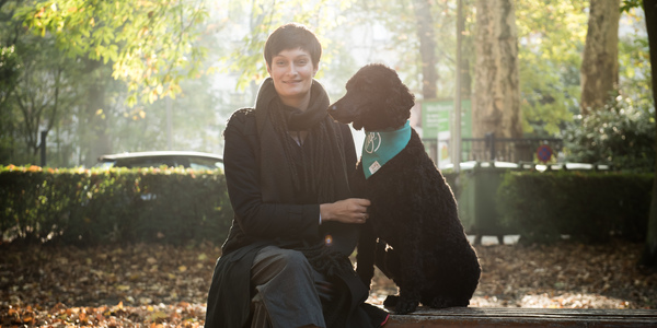 Joke Decru van AAP vzw met hond op een bankje in het bos