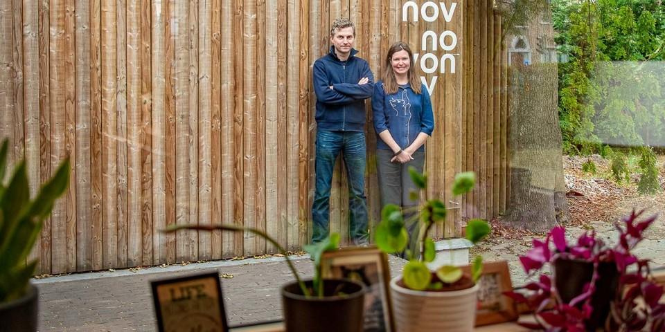 Benjamin en Liesbeth in de binnentuin van Novonov poserend voor een houten muur