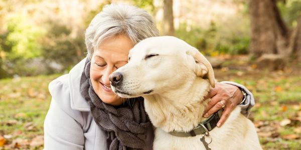 Een vrouw knuffelt een hond in het park.