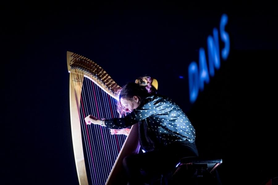 Een vrouw speelt harp op een dak in de nacht