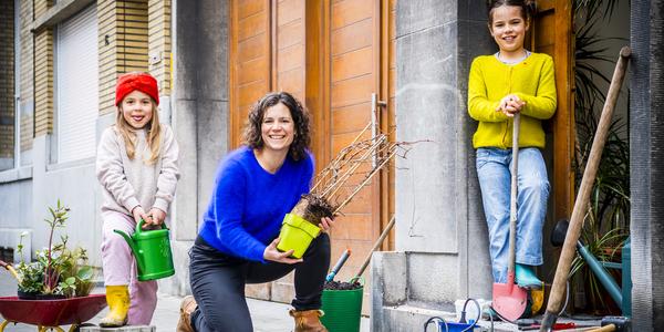 Een vrouw en 2 kinderen poseren voor de camera met een gieter, schop en planten.