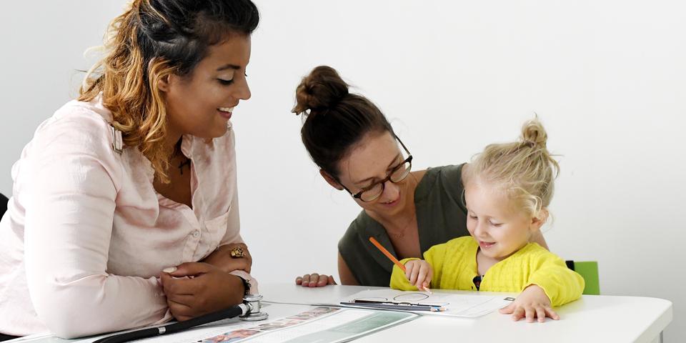 Een mama en haar dochter op bezoek bij een begeleidster van het Huis van het Kind