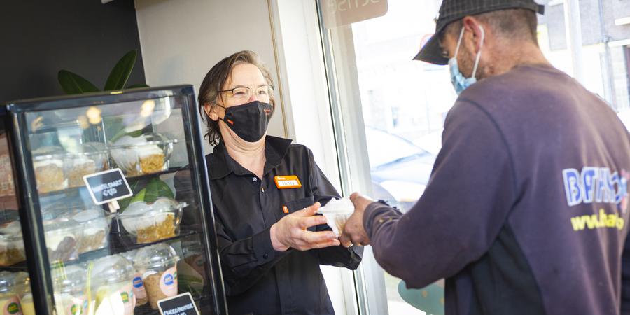 Een medewerker van het buurtrestaurant geeft een maaltijd in herbruikbare verpakking aan een klant.