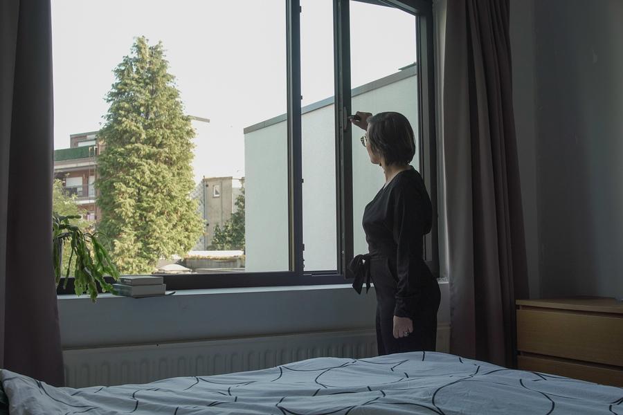 Een vrouw opent het raam in de slaapkamer om de woning te verluchten.