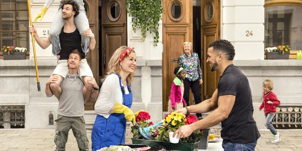 Mensen die de straat poetsen en opfleuren met bloemen