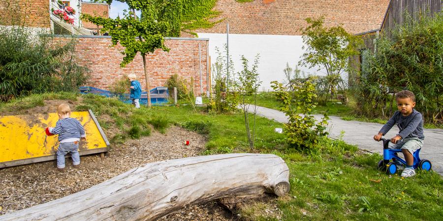 De groene en avontuurlijke buitenruimte van een kinderdagverblijf waarop peuters spelen