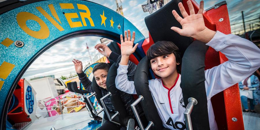 Een meisje en een jongen zitten met de handen in de lucht in een attractie van de Sinksenfoor.