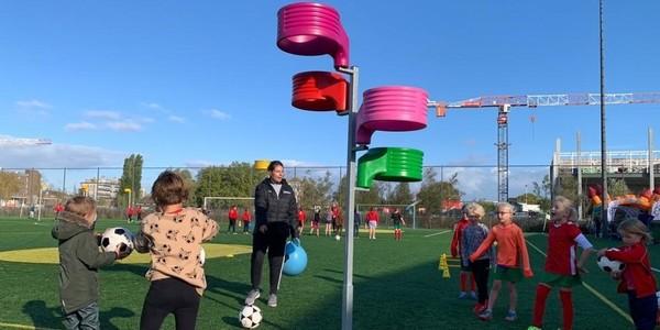 kinderen staan op een training samen met lesgeefster aan een korfbalpaal