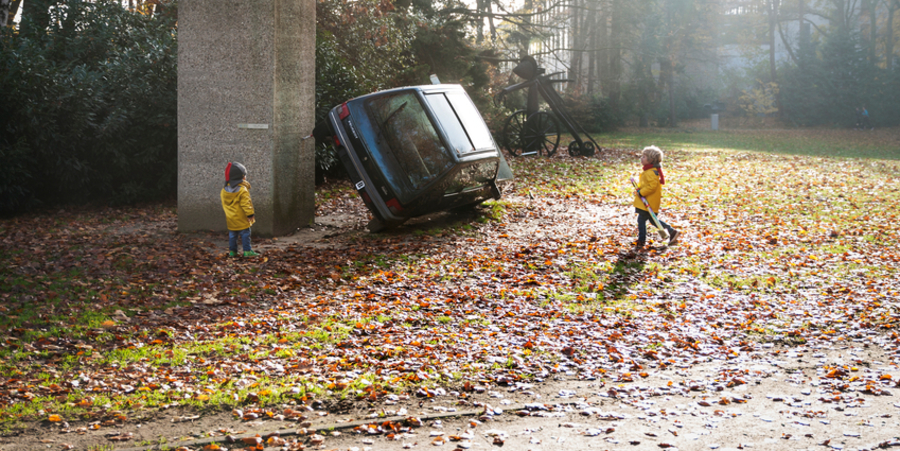 Twee kleine kinderen kijken in het kunstpark van het Middelheimmuseum naar een kunstwerk: een auto die zijwaarts op twee wielen staat.
