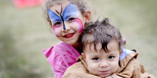 Een meisje is geschminkt als een vlinder en houdt een kindje in haar armen.