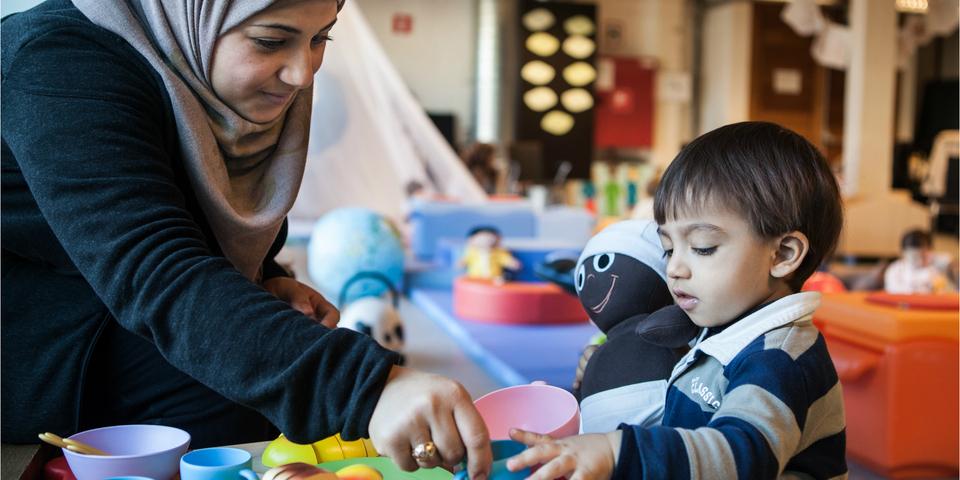 Een mama speelt met haar kind in een Huis van het Kind.