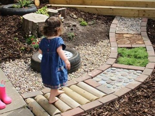 Meisje loopt over blotevoetenpad met verschillende materialen