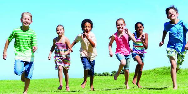 Zes kinderen lopen op een grasveld in de richting van de camera.