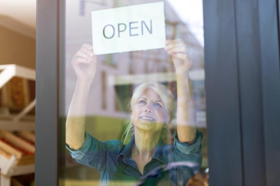 Een dame hangt een bordje 'open' op achter een etalage