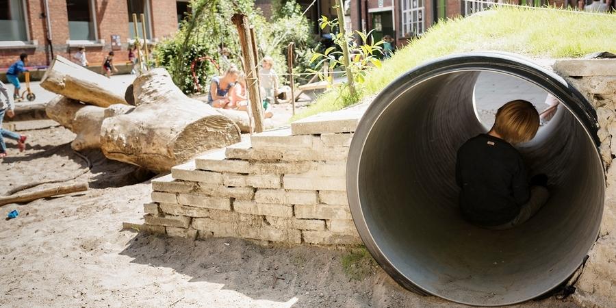 Een jongen zit rustig in de tunnel van een speelheuvel