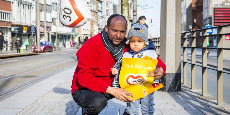 Een papa en zijn zoontje poseren met een affiche en een ballon waarop 'zone 30' staat.