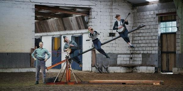 Muzikanten zitten op schuine balk. Een persoon staat ernaast.