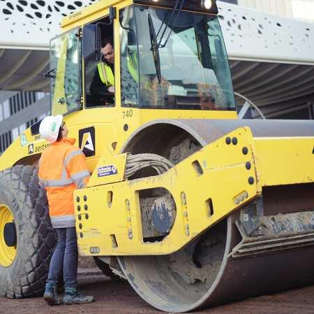 Werftoezichter praat met arbeider in voertuig
